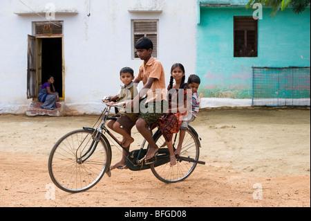 Indische Teenager und Kinder mit dem Fahrrad in einem indischen Dorf. Andhra Pradesh, Indien - Stockfoto