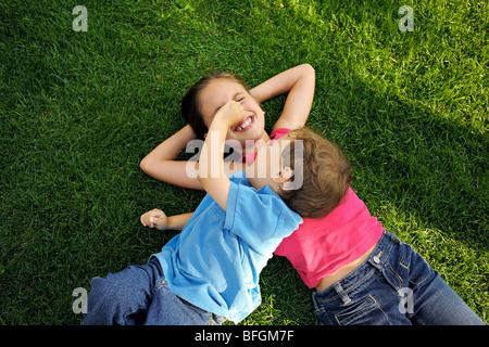Jungen und Mädchen, die Verlegung auf Rasen mit Händen hinter dem Kopf, Toronto, Ontario - Stockfoto