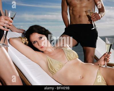 Frau im Bikini mit Champagner Glas mit Mann und Frau stehen in der Nähe von Meer - Stockfoto
