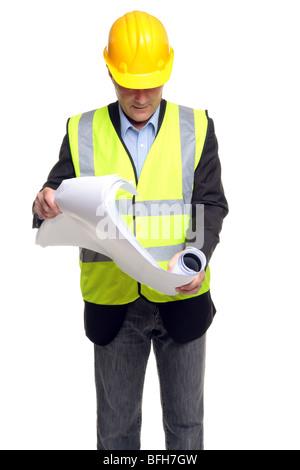 Bauunternehmer, Schutzkleidung zu tragen, wie er einige Blaupausen, isoliert auf einem weißen Hintergrund entfaltet. - Stockfoto