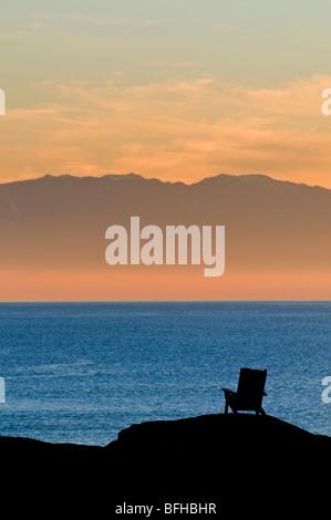 Ein Adirondack Stil Stuhl ist Silhouette gegen den Ozean und die Olympic Mountains bei Sonnenuntergang in der Nähe - Stockfoto