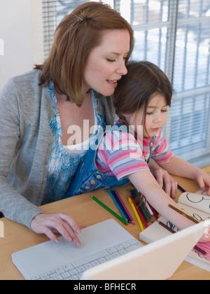 Mutter mit Laptop während Tochter Farben - Stockfoto