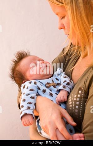 Eine junge Mutter wiegen ihres Neugeborenen Sohnes, der Schlaf in ihren Armen liegt. - Stockfoto