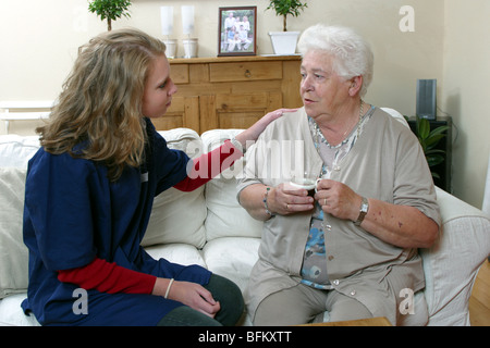 Junge Bezirk Krankenschwester im Gespräch mit einer alten Dame, die Unterstützung der älteren Person zu Hause und - Stockfoto