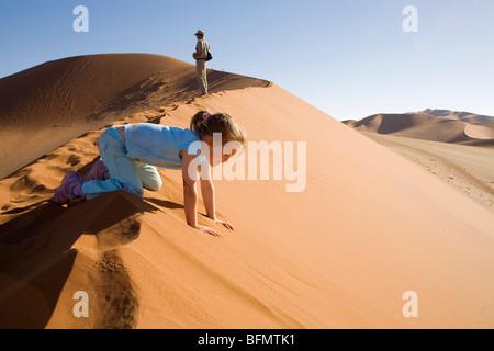 Sossusvlei, Namib-Naukluft-Nationalpark, Namibia. Einem jungen Mädchen und Safari Guide auf einer riesigen Sanddüne - Stockfoto