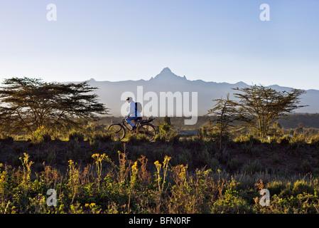 Kenia, Timau. In den frühen Morgenstunden Zyklen ein Mann mit Mount Kenia arbeiten im Hintergrund thront. - Stockfoto
