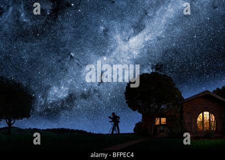 Ein Mann blickt auf die Milchstraße vor seinem Haus in der Nacht - Stockfoto