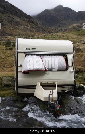 Eine Karawane in Llanberis Pass Snowdonia geblasen von der Straße über den Fluss in den November 2009 stürmen. - Stockfoto