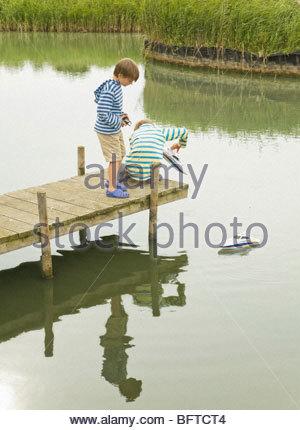 Jungs spielen mit Spielzeug Boot am Steg - Stockfoto