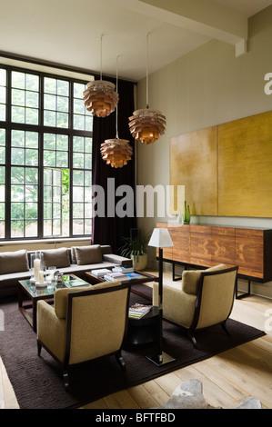 Wohnzimmer mit Artischocke Lichter, große Fenster und Kunstwerke. - Stockfoto