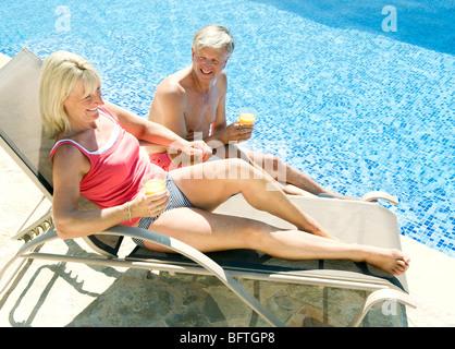 Ein älteres Paar am Pool im Gespräch - Stockfoto
