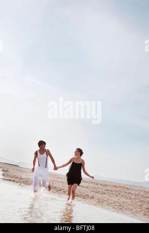 paar am Strand entlang laufen - Stockfoto