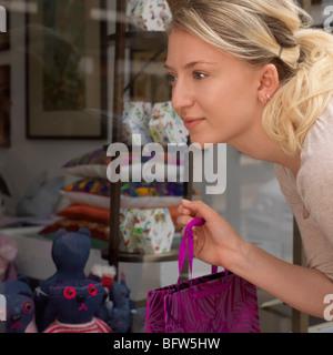 junge Frau, die Schaufenster betrachten - Stockfoto