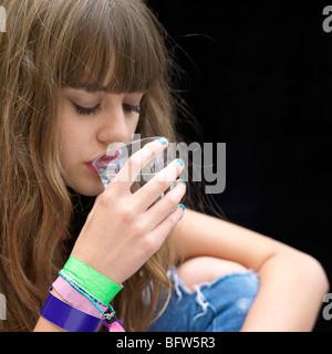 junge Frau trinken aus einem Glas - Stockfoto