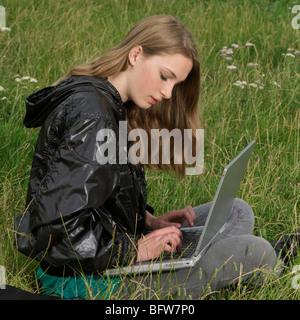 junge Frau mit Laptop im park - Stockfoto