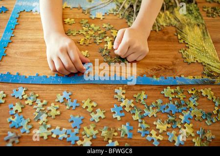 Einige Hände arbeiten auf ein puzzle - Stockfoto