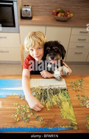Ein Junge hält einen Hund dabei eine puzzle - Stockfoto