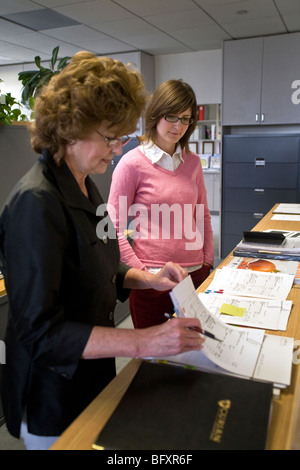 Frauen-Büroangestellte überprüfen Sie über Papiere für einen Kunden in einer Finanzberatung Kanzlei in Irvine, Kalifornien. - Stockfoto