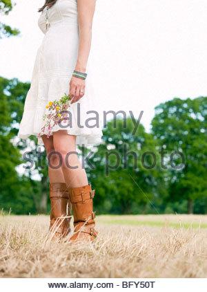 Frau im Feld halten Blumen - Stockfoto
