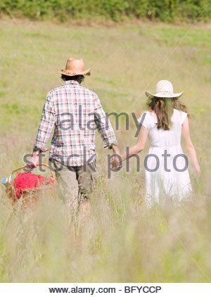 paar in Hüte zu Fuß durch Wiese - Stockfoto