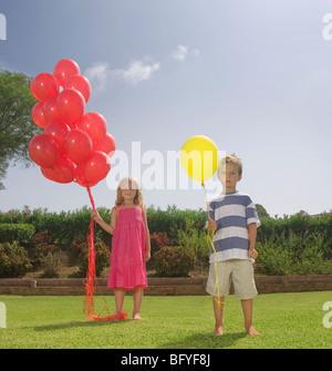 Kleine Kinder halten rote Luftballons - Stockfoto