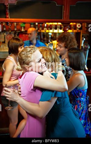 Zwei Mädchen umarmt in Pub/bar - Stockfoto