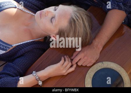 paar auf Deck Hand in Hand liegend - Stockfoto