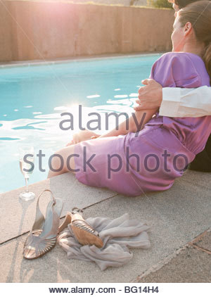 paar saß neben Schwimmbad, umarmt - Stockfoto