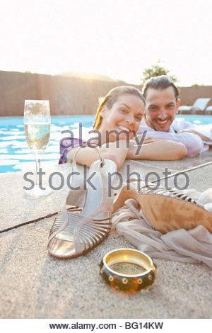 paar lächelnd im Pool, gekleidet - Stockfoto
