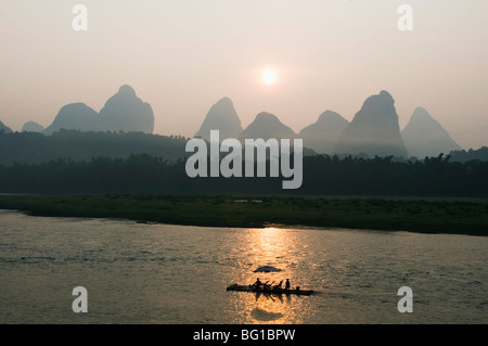 Touristenboot Segeln durch die Karst-Landschaft bei Sonnenaufgang auf dem Li-Fluss (Lijiang) in Yangshuo, nr Guilin, - Stockfoto