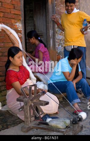 Eine Frau dreht Wolle, während andere, bei dem kleinen Dorf Bungamati, Nepal reden - Stockfoto