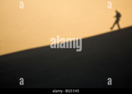 Schatten eines Mannes hinunter eine Sanddüne - Stockfoto
