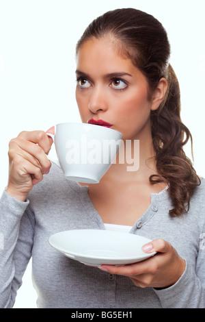 Ein Frau trinken Tee aus einer Tasse und Untertasse wie denkt über etwas, weißer Hintergrund. - Stockfoto