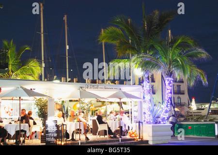 Weihnachtsbeleuchtung um Palmen außerhalb Straßencafé in Puerto de Mogan auf Gran Canaria - Stockfoto