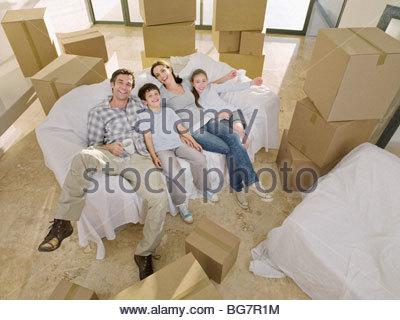 Familie Verlegung auf Sofa umgeben von Kartons - Stockfoto