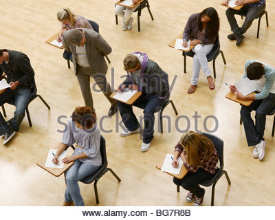 Professor zu Fuß von College-Studenten unter Test im Klassenzimmer - Stockfoto