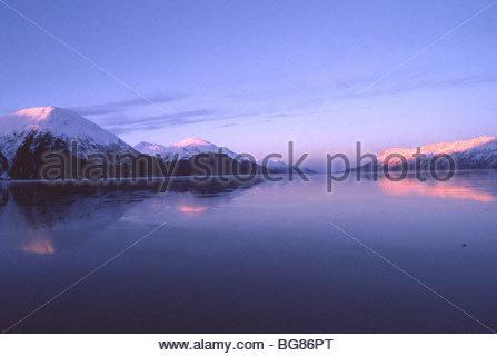 Die Sonnenaufgänge über Turnagain Arm im Winter gießen ein Morgen Alpenglühen auf den Gipfeln der Chugach Mountains. - Stockfoto
