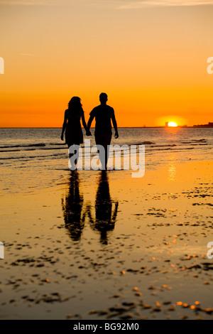 Junge Paare, die einen Strand bei Sonnenauf- oder Sonnenuntergang. - Stockfoto