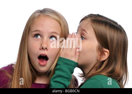 Zwei Mädchen erzählen ein Geheimnis und wundern isoliert auf weiss - Stockfoto