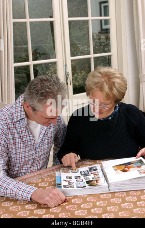 Aufgewachsen, Sohn besuchen ältere Mutter, zeigt Bilder im Fotoalbum - Stockfoto