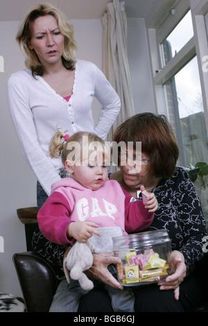 Großmutter, die Kinder mit Süßigkeiten Süßigkeiten und Mutter verärgert zu verderben. - Stockfoto