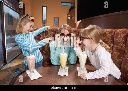 Mutter und Töchter teilen Milchshakes und tragen Nase und Brillen - Stockfoto