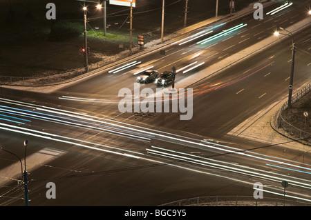 Nachtaufnahme: Kreuzung in St. Petersburg Stadt Linien ab Scheinwerfer des Autos unterwegs. Zwei Autos wartet ein - Stockfoto