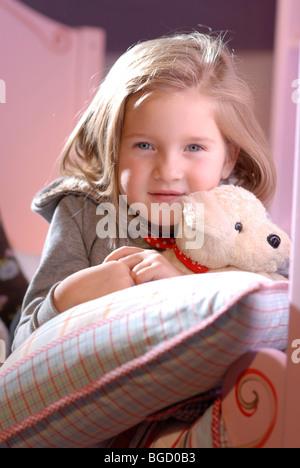 Kleines Mädchen mit ihrem Stofftier Lyubg zwischen Kissen auf ihrem Bett - Stockfoto