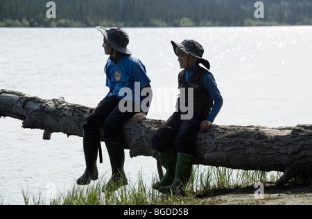 Im Urlaub, Geschwister, 12 Jahre altes Mädchen und 6 Jahre alten Jungen, sitzen auf einem Baumstamm, Teslin River, - Stockfoto