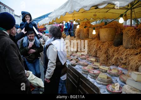 Stock Foto eines Kindes auf eine Erwachsene Schultern ein Stück Käse gegeben durch einen französischen Markt Standinhaber - Stockfoto