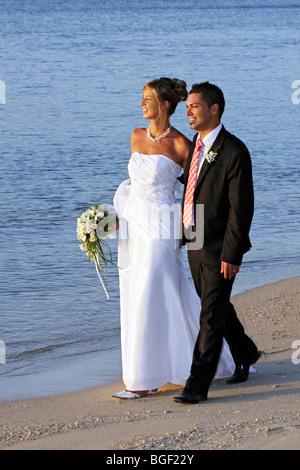 Braut und Bräutigam zu Fuß am Strand - Stockfoto