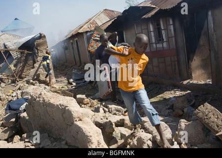Ein Junge flieht seine brennenden Nachbarschaft in Kenia nach den Wahlen Unruhen, Kisumu, Kenia. - Stockfoto