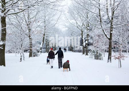 Familie Kinder Rodeln auf der verschneiten Avenue flanieren - Stockfoto
