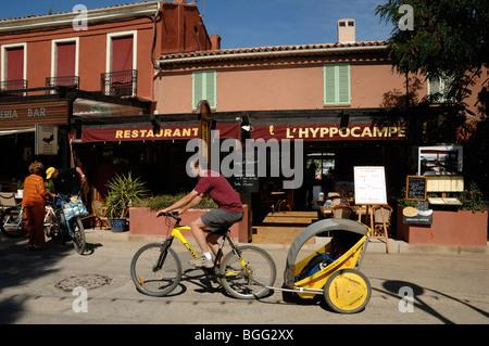 Radfahrer mit Kind Trailer Zyklen Vergangenheit Restaurants auf der Insel Porquerolles, Îles Hyères, Var, Côte d - Stockfoto